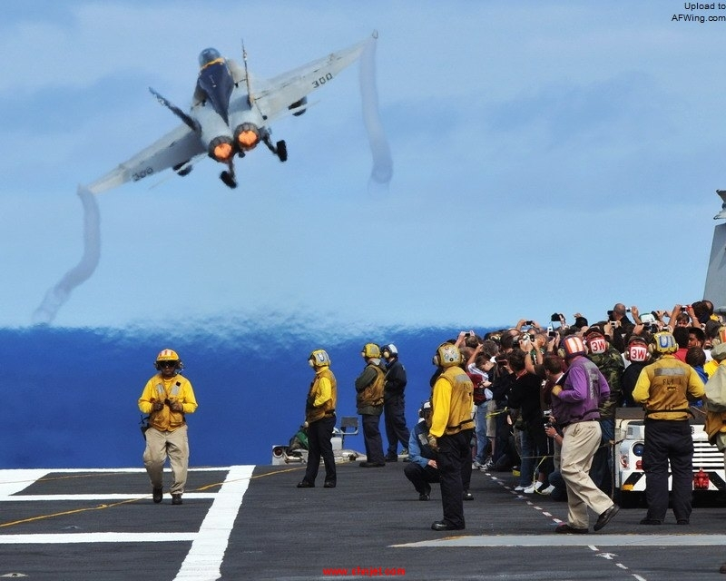 US_Navy_081006-N-7981E-278_Tiger_Cruise_participants_aboard_the_aircraft_carrier_USS_Abraham_Lincoln_%28CVN_72%29_watch_from_behind_the_flight_deck_foul_lines_as_an_F-A-18C_Hornet_assigned_to.jpg
